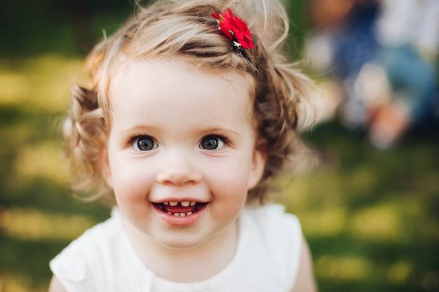 Schließen sie oben vom gesicht des lächelnden schönen babymädchens auf natursommer beim aufstellen an der kamera