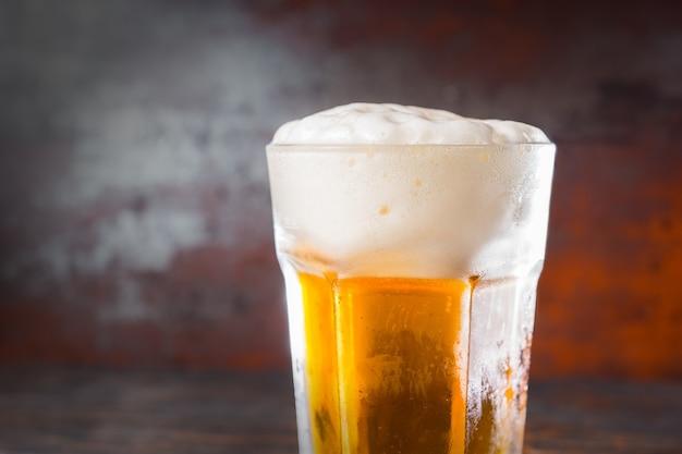 Schließen sie oben vom glas mit einem hellen bier und einem großen schaumkopf auf altem dunklem schreibtisch. getränke- und getränkekonzept