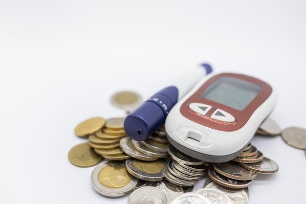Schließen sie oben vom glukosemeter mit lanzette für kontrollblutzuckerspiegel auf stapel von münzen.