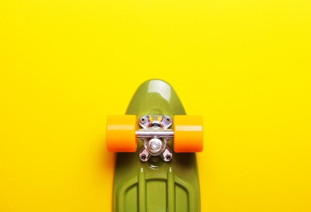 Schließen sie oben vom grünen skateboard mit orange rädern auf gelbem hintergrund.