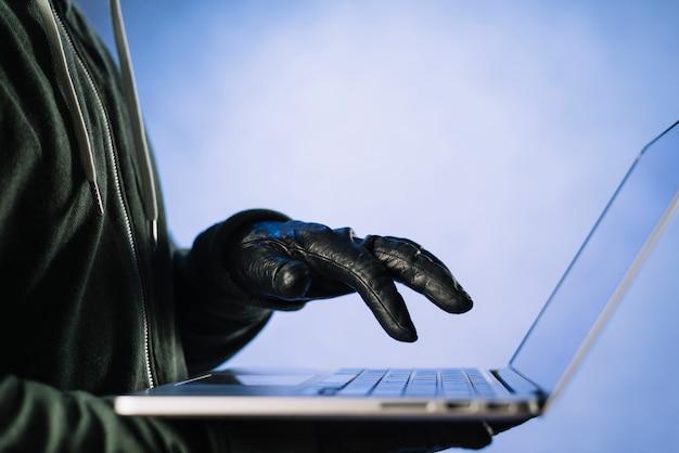 Schließen sie oben vom hacker, der auf laptop schreibt