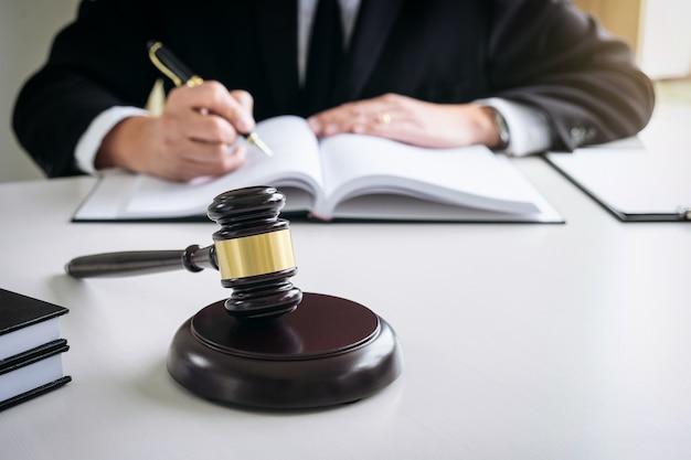 Schließen sie oben vom hammer, vom männlichen rechtsanwalt oder vom richter, die mit gesetzbüchern arbeiten, berichten sie den fall auf tabelle