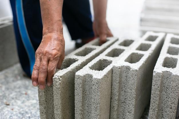 Schließen sie oben vom industriellen maurer, der ziegelsteine auf baustelle, errichtende wände installiert.
