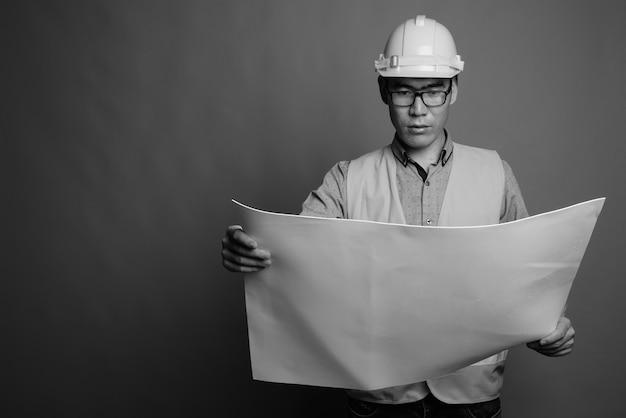 Schließen sie oben vom jungen asiatischen mannbauarbeiter, der brillen trägt