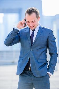 Schließen sie oben vom jungen geschäftsmann, der nahe dem modernen flughafen geht. mit dem telefon sprechen. klassisch gekleidet.