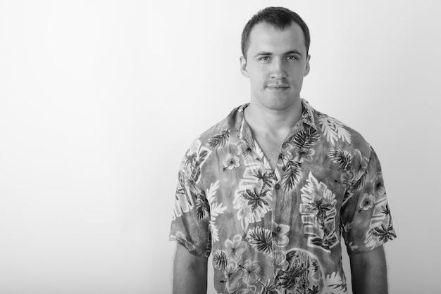Schließen sie oben vom jungen touristenmann, der hawaiihemd bereit für urlaub in schwarzweiss trägt
