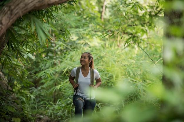 Schließen sie oben vom jungen wanderer, der durch den wald geht, der mit natur glücklich ist.