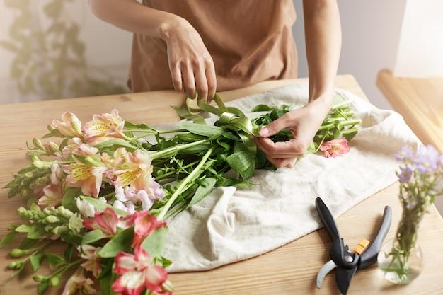 Schließen sie oben vom jungen weiblichen floristen, der band am blumenstrauß am arbeitsplatz bindet.