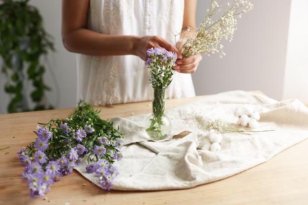 Schließen sie oben vom jungen weiblichen floristen, der mit blumenstrauß am arbeitsplatz arbeitet.