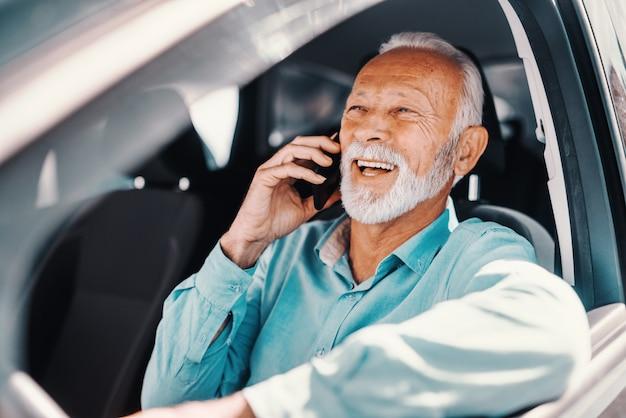 Schließen sie oben vom lächelnden bärtigen senior, der am telefon mit arm am geöffneten fenster spricht, während sie im auto sitzen.