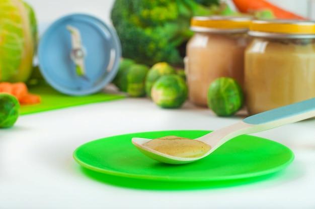 Schließen sie oben vom löffel mit natürlicher babynahrung auf tisch