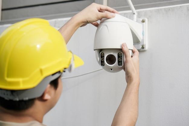 Schließen sie oben vom männlichen techniker, der überwachungskamera auf wand repariert
