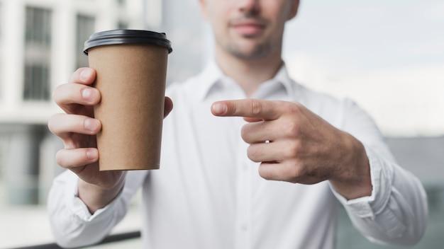 Schließen sie oben vom mann, der auf kaffee zeigt