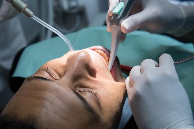 Schließen sie oben vom mann, der die mundhöhle des jungen afroamerikanermannes überprüft, der herein in der zahnmedizinischen klinik mit assistenten arbeitet.