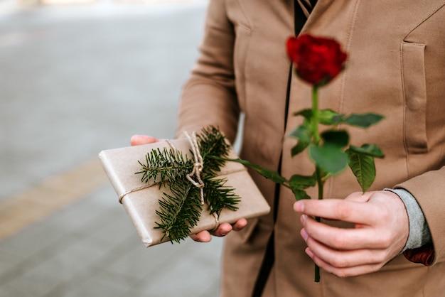 Schließen sie oben vom mann, der eine rose und ein geschenk gibt. valentinstag.