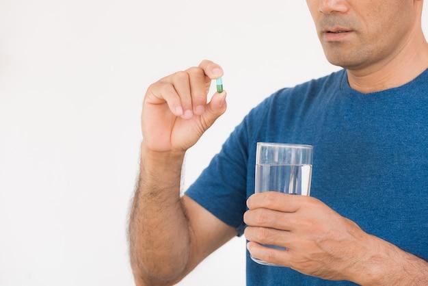 Schließen sie oben vom mann, der pille einläßt und eine andere hand, die ein glas wasser hält.