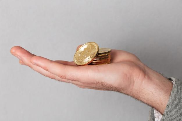 Schließen sie oben vom mann, der stapel goldene bitcoins zeigt
