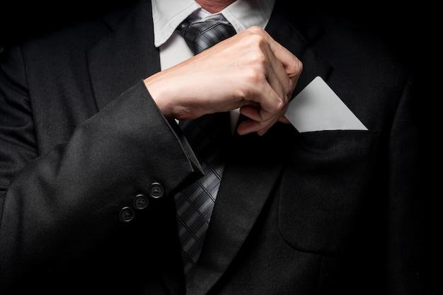 Schließen sie oben vom mann im schwarzen anzug, der visitenkarte auf schwarzem hintergrund hält