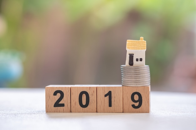 Schließen sie oben vom miniaturhausmodell auf stapel silbermünzen auf holzklotzzahl 2019.