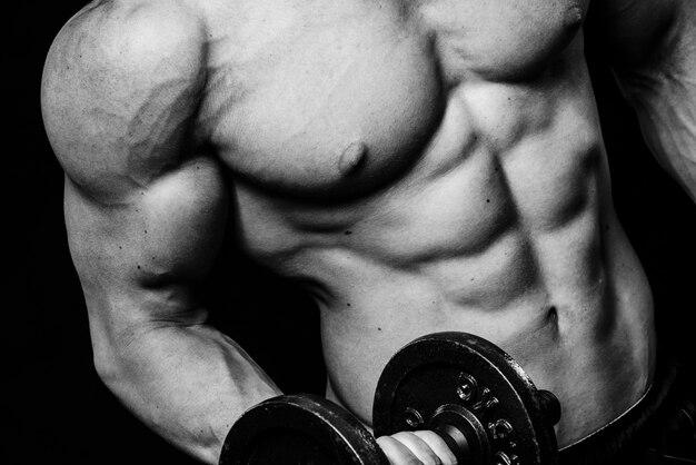 Schließen sie oben vom muskulösen bodybuilderkerl, der übungen mit gewichtsdummkopf über lokalisierter schwarzer wand tut. schwarz und weiß