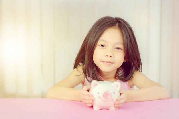 Schließen sie oben vom netten kleinen mädchen mit sparschwein, kindereinsparungskonzept.