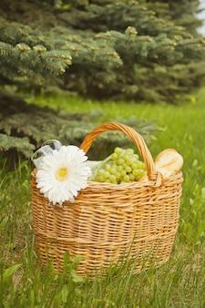 Schließen sie oben vom picknickkorb mit lebensmittel, früchten und blume auf der gelben abdeckung auf dem grünen gras