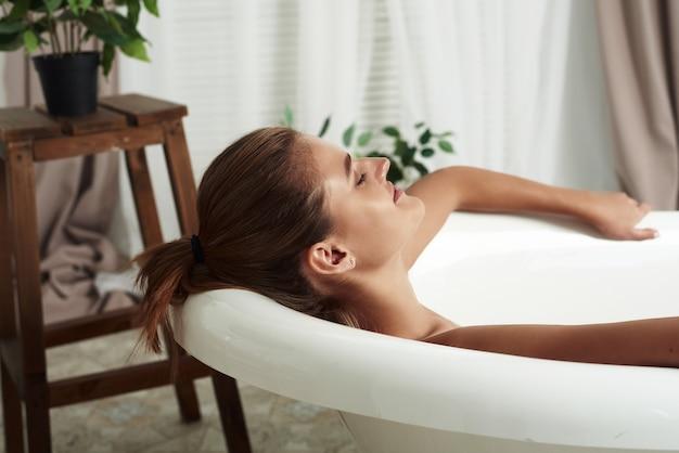 Schließen sie oben vom porträt der glücklichen hübschen frau mit attraktivem lächeln, das sich entspannt, während sie in der hellen wohnung während der romantischen atmosphäre baden.