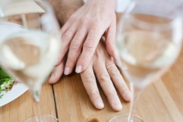 Schließen sie oben vom reifen paar, das eheringe auf romantischem esstisch im restaurant trägt, kopieren sie raum