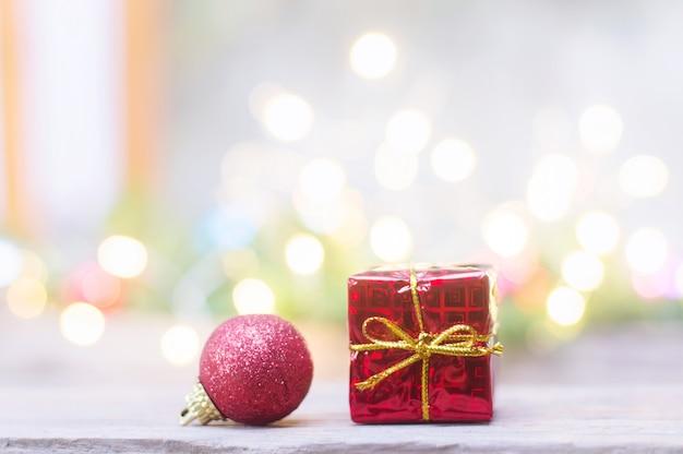 Schließen sie oben vom roten ball und von der roten geschenkbox für weihnachts- oder des neuen jahresdekorationshintergrund