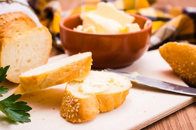 Schließen sie oben vom sandwich mit butter und geschnittenem stangenbrot auf einem schneidebrett
