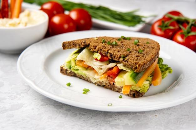 Schließen sie oben vom sandwich mit hummus und gemüse auf weißem teller