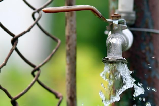 Schließen sie oben vom schmutzmessinghahn auf grünem bokeh hintergrund. wasserknappheit und tag der erde-konzept.