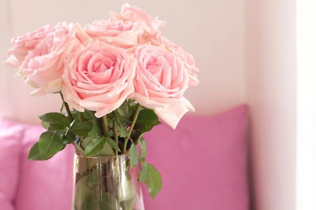Schließen sie oben vom schönen blumenstrauß von rosa rosen im glasvase auf tabelle am wohnzimmer.