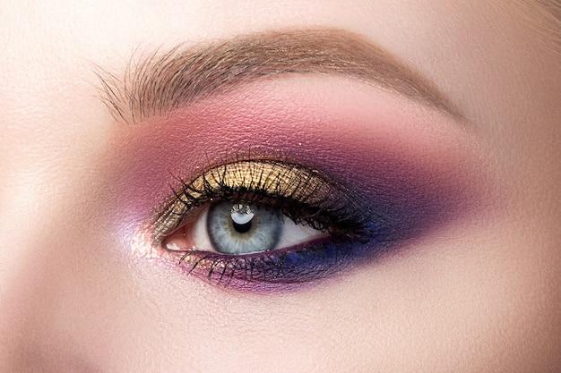 Schließen sie oben vom schönen frauenauge mit dem mehrfarbigen rauchigen augen make-up. moderne mode schminken.