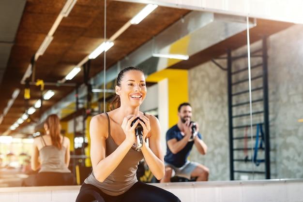Schließen sie oben vom schönen lächelnden kaukasischen mädchen mit pferdeschwanz, der übungen mit kettlebell tut. im hintergrundspiegel und mann im spiegelbild.
