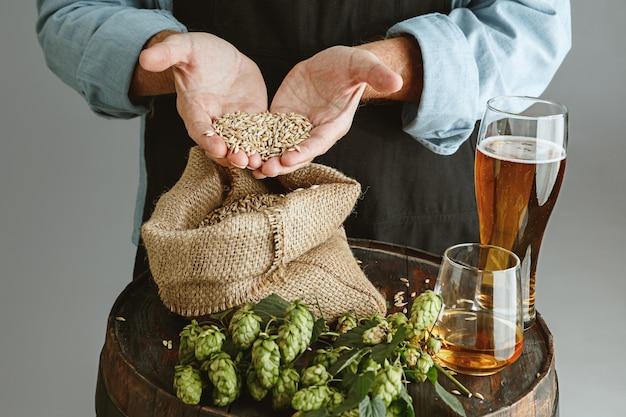 Schließen sie oben vom selbstbewussten älteren mannbrauer mit selbst hergestelltem bier im glas auf holzfass auf grau