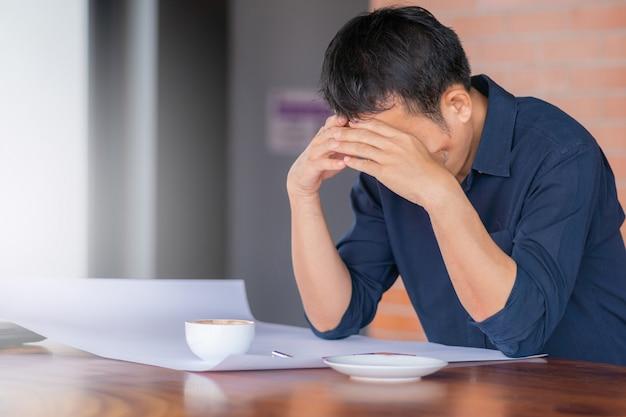 Schließen sie oben vom sitzenden kopf des zufälligen ernsten mannes in den händen im büro