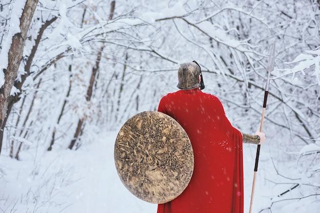 Schließen sie oben vom spartanischen mann, der im winterwald steht