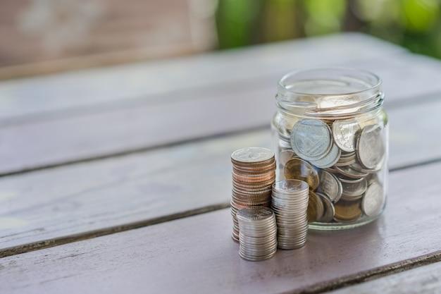 Schließen sie oben vom stapel münzen in einem glas-, geschäfts-, finanz-, einsparungens- oder managementgeld