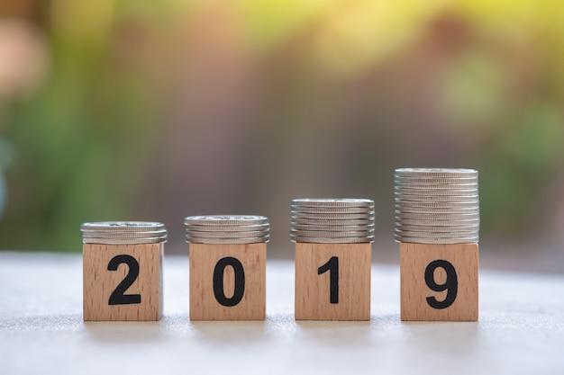 Schließen sie oben vom stapel silbermünzen auf 2019 hölzernen zahlenblöcken.