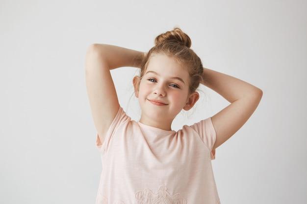 Schließen sie oben vom süßen kleinen blonden mädchen mit brötchenfrisur im rosa lächelnden rosa t-shirt, händchenhalten hinter dem kopf mit glücklichem und zufriedenem ausdruck.
