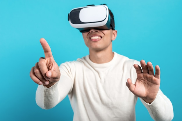 Schließen sie oben vom tragenden kopfhörer der virtuellen realität des lustigen mannes auf blau