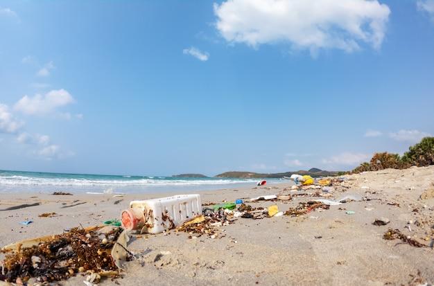Schließen sie oben vom trödelabfall, der auf dem strandumweltverschmutzungshintergrund schmutzig ist.
