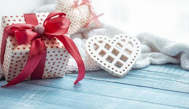Schließen sie oben vom valentinstaggeschenk und vom dekorativen herzen auf einer hölzernen oberfläche. das konzept des urlaubs aller liebenden.