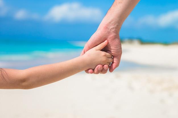 Schließen sie oben vom vater und von kleinkind, die hände am strand sich halten
