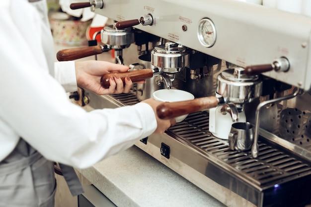 Schließen sie oben vom weiblichen barista, der kaffee zubereitet