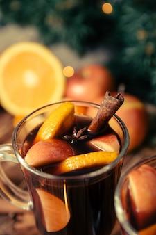 Schließen sie oben vom weihnachtsglühwein mit früchten und gewürzen auf holztisch