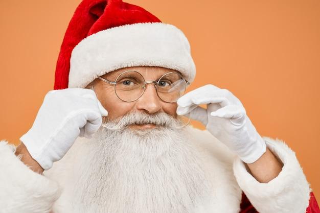 Schließen sie oben von älterer santa claus, die schnurrbart im studio wirbelt