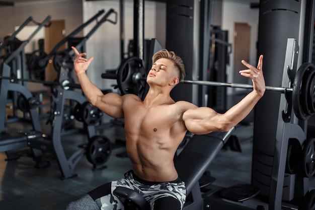 Schließen sie oben von anhebenden gewichten eines muskulösen jungen mannes in der turnhalle auf dunklem hintergrund