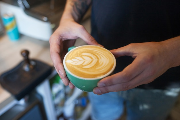Schließen sie oben von barista, der aromatischen cappuccino hält. kaffee zum verkauf bereit. männliche hände, die eine tasse kaffee halten.